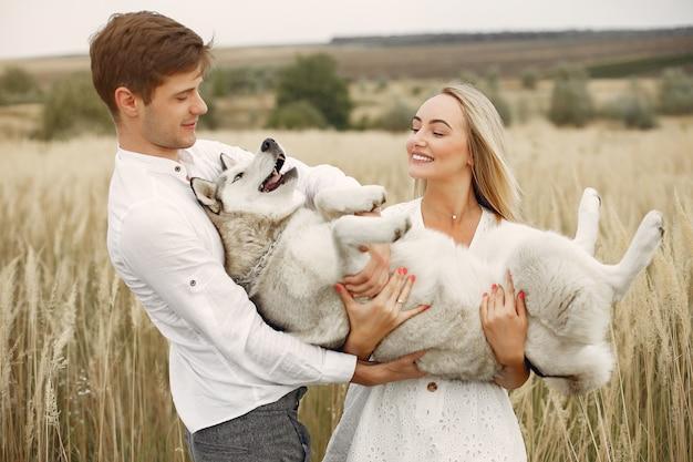 Couple dans un champ d'automne jouant avec un chien