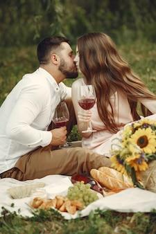 Couple dans un champ. brunette en robe blanche. paire assis sur l'herbe.