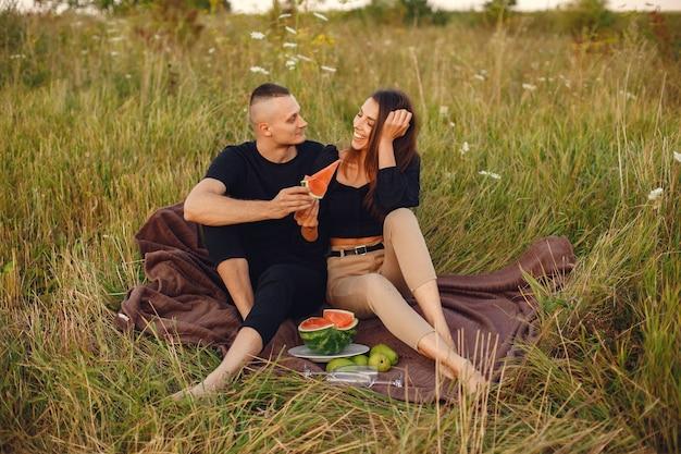 Couple dans un champ. femme dans un chemisier noir. les gens avec de la pastèque.