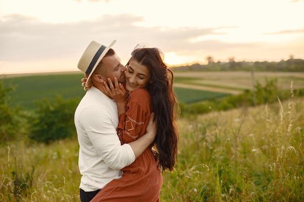 Couple dans un champ. femme en robe marron.