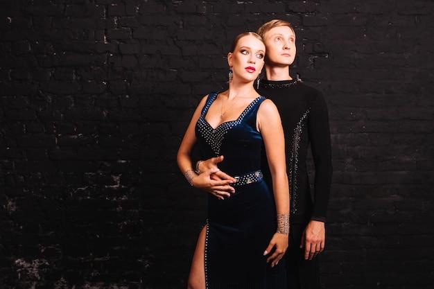 Couple dans les costumes de la salle de bal près de mur noir