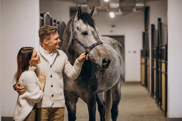 Couple dans l'écurie avec cheval