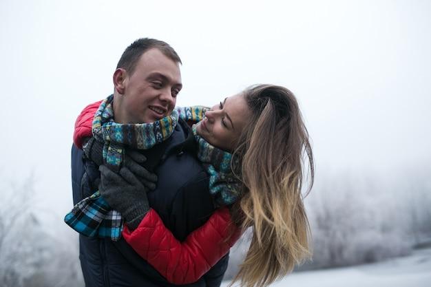 Couple dans la forêt d'hiver près du lac