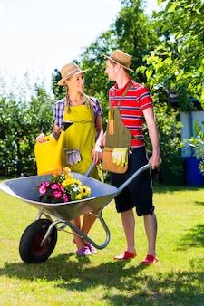 Couple dans le jardin avec arrosoir et brouette