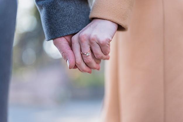 Couple, dans, manteaux, tenant mains