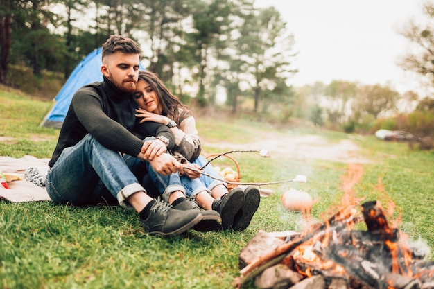 Couple dans la nature, faire griller des guimauves