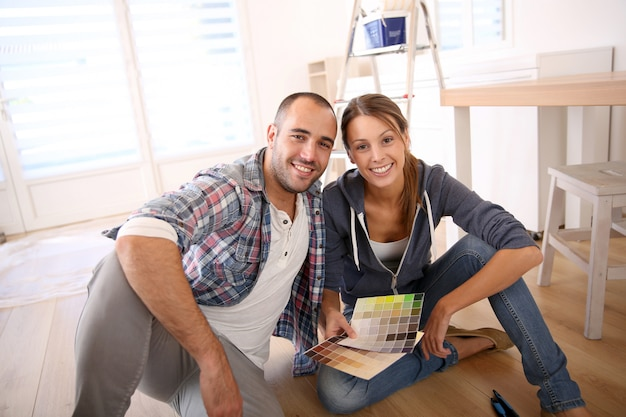 Couple dans la nouvelle maison en choisissant la couleur pour les murs