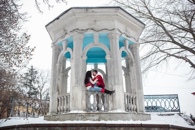 Couple dans le pavillon en pierre en hiver