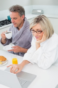 Couple dans des peignoirs avec du café et du jus en utilisant un ordinateur portable dans la cuisine
