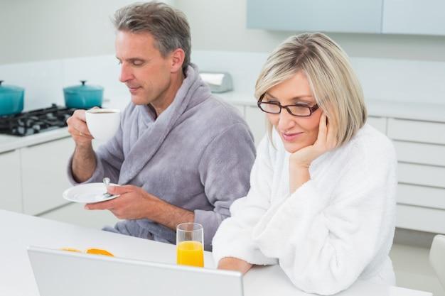 Couple dans des peignoirs avec du café et du jus en utilisant un ordinateur portable
