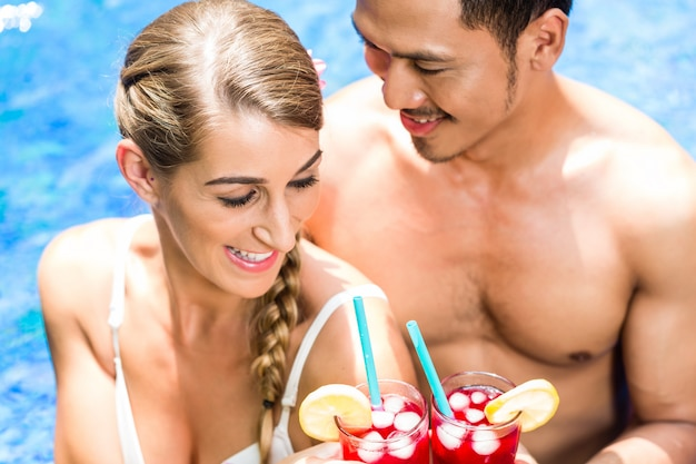 Couple dans une piscine asiatique en buvant des cocktails