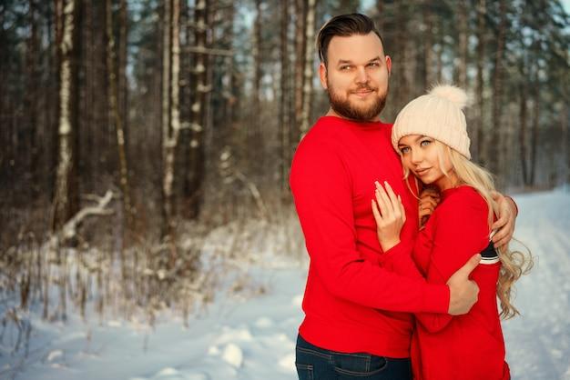 Le couple dans le pull rouge en hiver dans la forêt happy hug romance