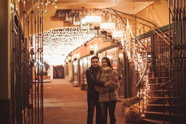 Couple dans la rue avant noël. toile de fond de décorations de lumières bokeh