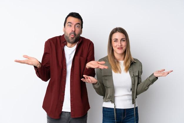 Couple dans la saint-valentin sur un mur isolé ayant des doutes et avec une expression de visage confuse