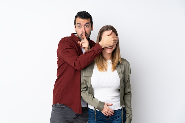Couple dans la saint-valentin sur un mur isolé couvrant ses yeux pour la surprendre