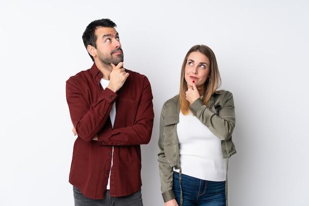 Couple dans la saint-valentin sur mur isolé debout et penser à une idée