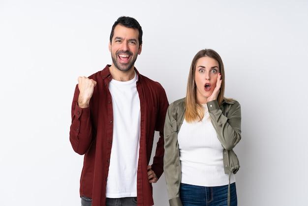 Couple dans la saint-valentin sur mur isolé pointant le doigt sur le côté et présentant un produit