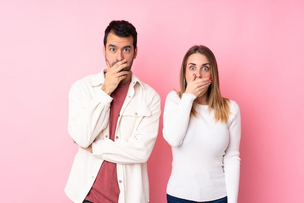 Couple dans la saint valentin sur un mur rose isolé couvrant la bouche avec les mains pour avoir dit quelque chose d'inapproprié