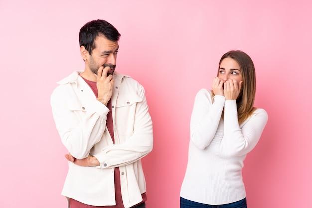 Couple dans la saint-valentin sur un mur rose isolé est un peu nerveux et effrayé mettant les mains à la bouche