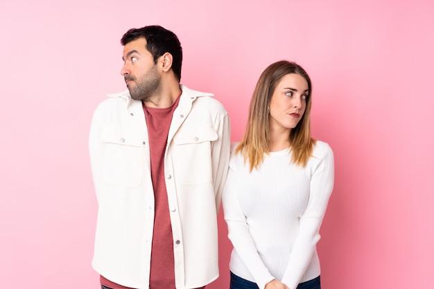 Couple dans la saint-valentin sur mur rose isolé nerveux et effrayé