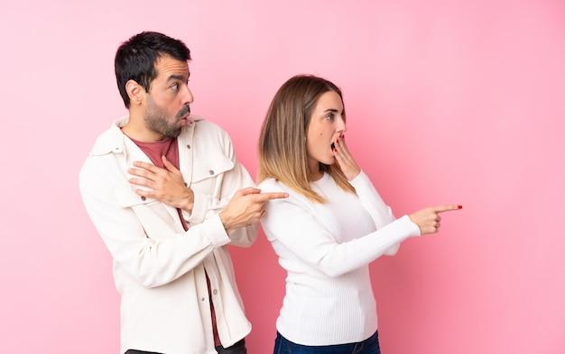 Couple dans la saint-valentin sur mur rose isolé pointant le doigt sur le côté avec un visage surpris