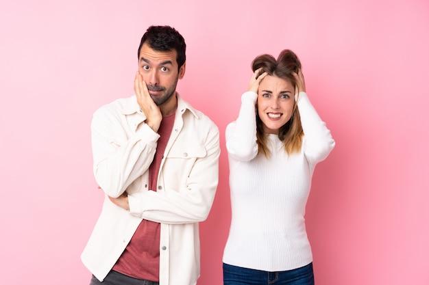 Couple dans la saint-valentin sur un mur rose isolé prend les mains sur la tête parce qu'il a la migraine