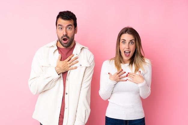 Couple dans la saint-valentin sur un mur rose isolé surpris et choqué tout en regardant à droite