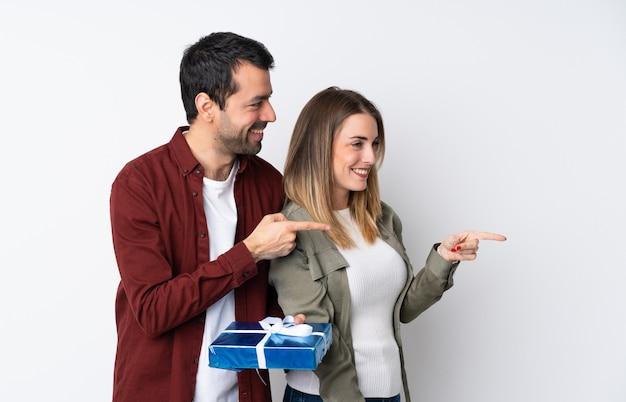 Couple dans la saint-valentin tenant un cadeau sur le mur isolé pointant le doigt sur le côté