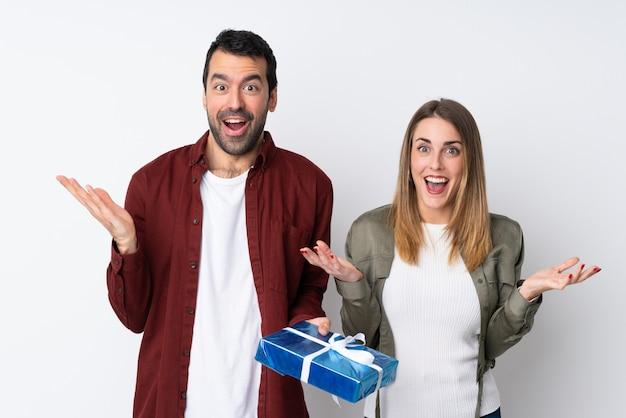 Couple dans la saint-valentin tenant un cadeau sur un mur isolé avec surprise et expression faciale choquée
