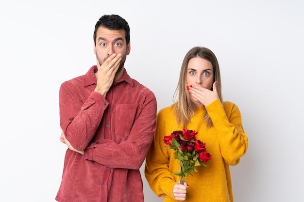 Couple dans la saint-valentin tenant des fleurs sur un mur isolé couvrant la bouche avec les mains pour avoir dit quelque chose d'inapproprié