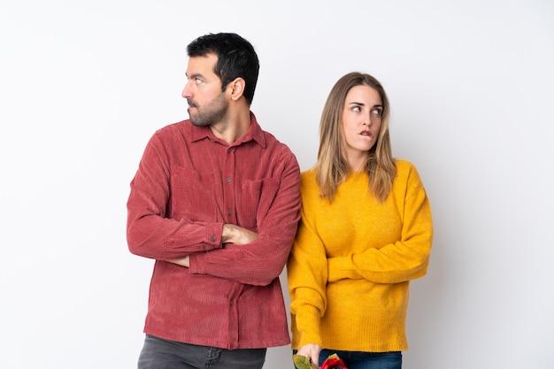 Couple dans la saint-valentin tenant des fleurs sur un mur isolé avec une expression de visage confuse tout en mordant la lèvre