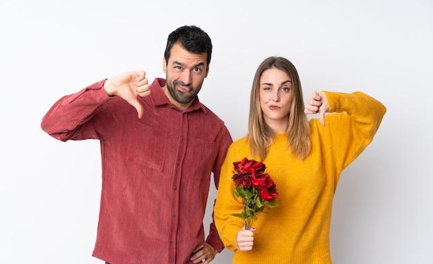 Couple dans la saint-valentin tenant des fleurs sur un mur isolé montrant le pouce vers le bas avec les deux mains