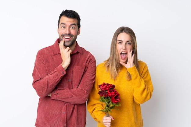 Couple dans la saint-valentin tenant des fleurs sur un mur isolé surpris et choqué tout en regardant à droite