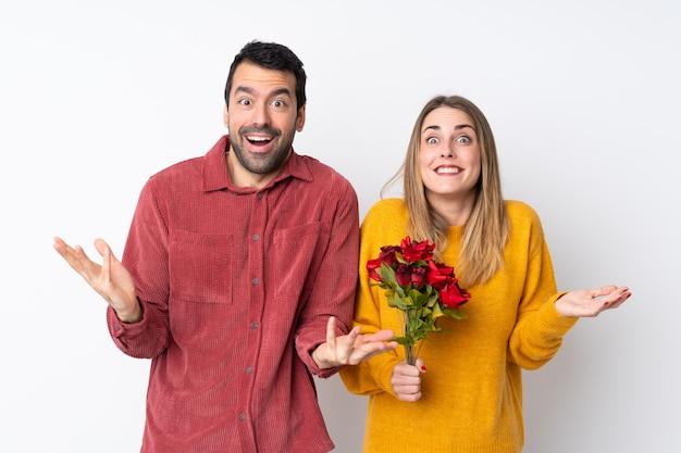 Couple dans la saint-valentin tenant des fleurs sur un mur isolé avec surprise et expression faciale choquée