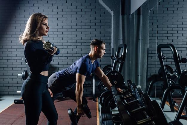 Couple dans la salle de fitness avec haltères, soulever du poids comme sport, homme et femme s'entraînant ensemble