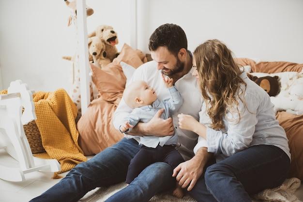 Couple dans la salle de séjour avec bébé souriant