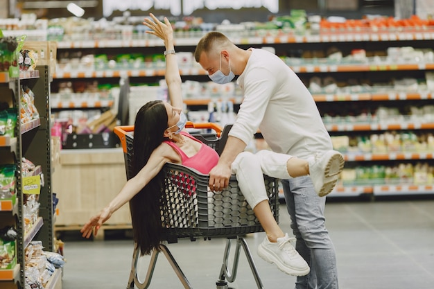 Couple dans un supermarché. dame dans un masque médical. les gens font des parachutes.