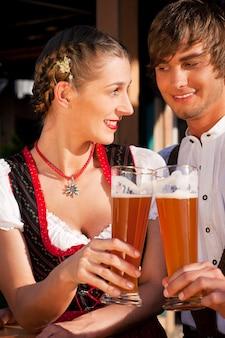 Couple dans une tracht bavaroise buvant de la bière de blé