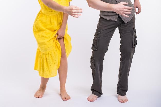 Couple dansant la musique latine. bachata, merengue, salsa et kizomba. gros plan de l'élégance des jambes pose sur salle blanche.