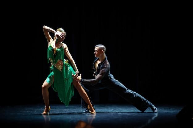 Couple de danse de salon isolé sur fond noir.