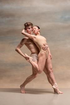 Couple de danseurs de ballet posant sur un espace gris