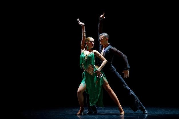 Couple de danseurs sur fond noir isolé. bel homme musclé et jolie femme blonde