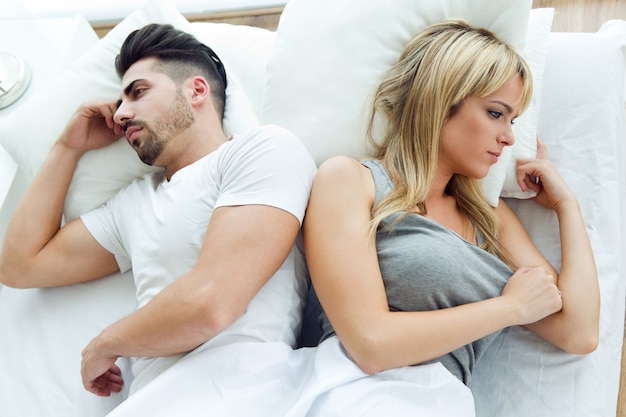 Un couple débordant couché en arrière dans le lit