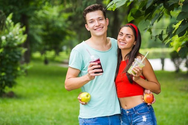 Couple, debout, dans, parc, tenue, sain, smoothies, et, pommes