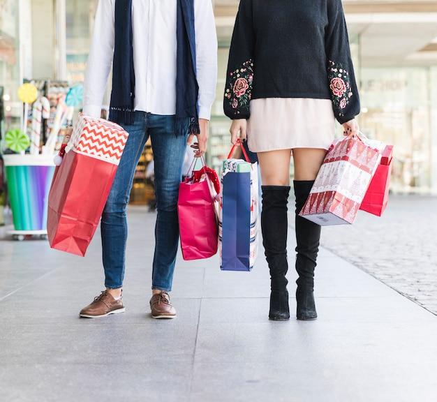 Couple debout dans la rue avec des sacs