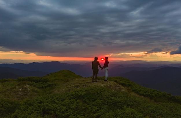 Le couple debout sur le fond lumineux du coucher de soleil