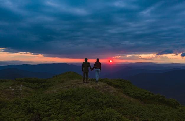 Le couple debout sur le fond lumineux du lever du soleil