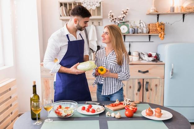 Couple debout avec des légumes à la table