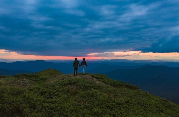 Le couple debout sur le magnifique fond de coucher de soleil