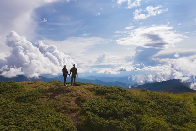 Le couple debout sur une montagne contre de beaux nuages